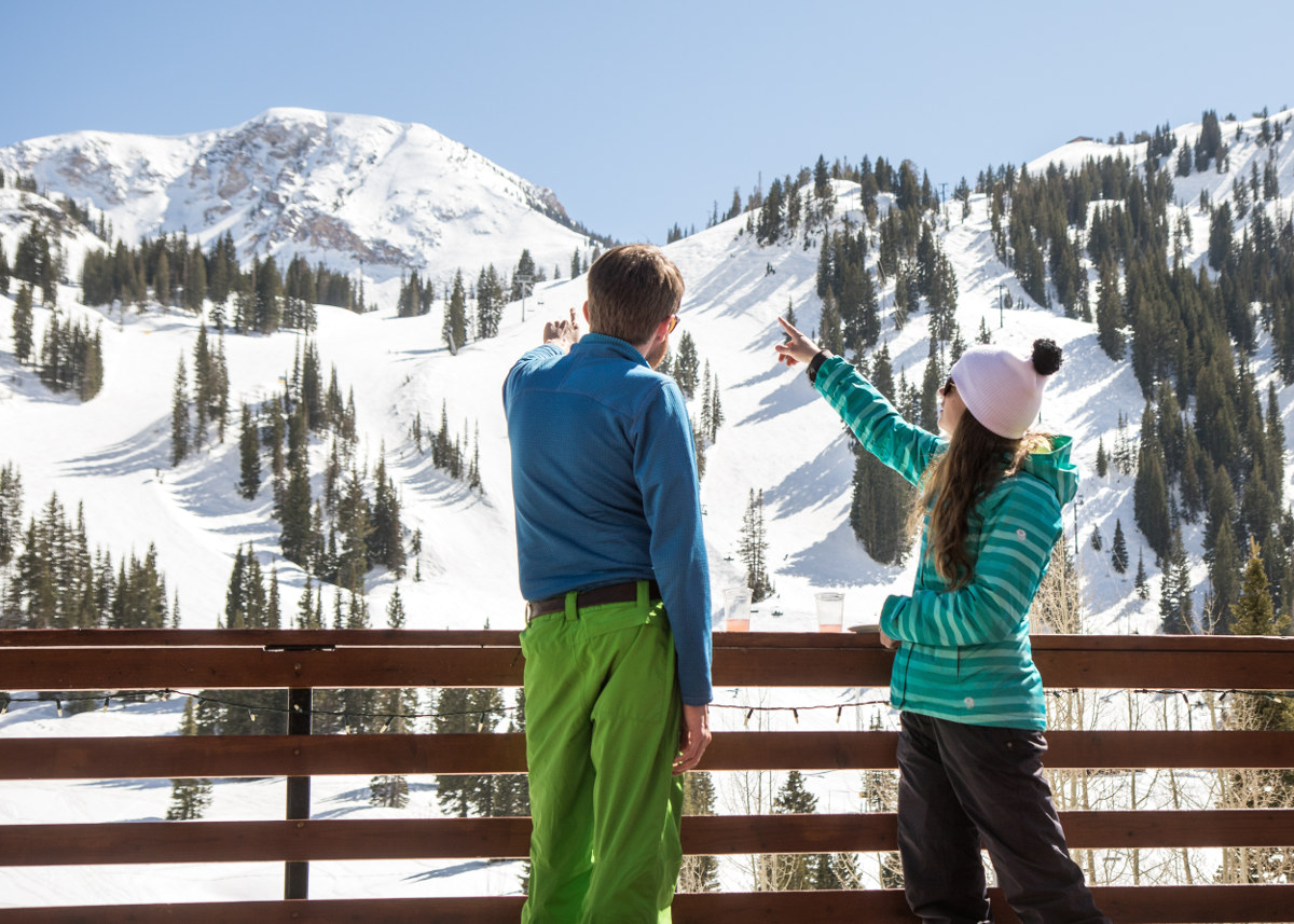 Two skiers pointing out ski runs on the deck of the Alta Lodge.