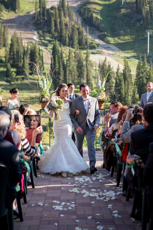 Bride and groom walk down the aisle with mountains in background | mountain wedding