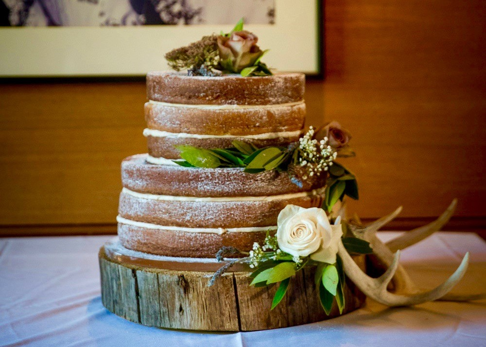 Un-iced, rustic wedding cake with wood base.