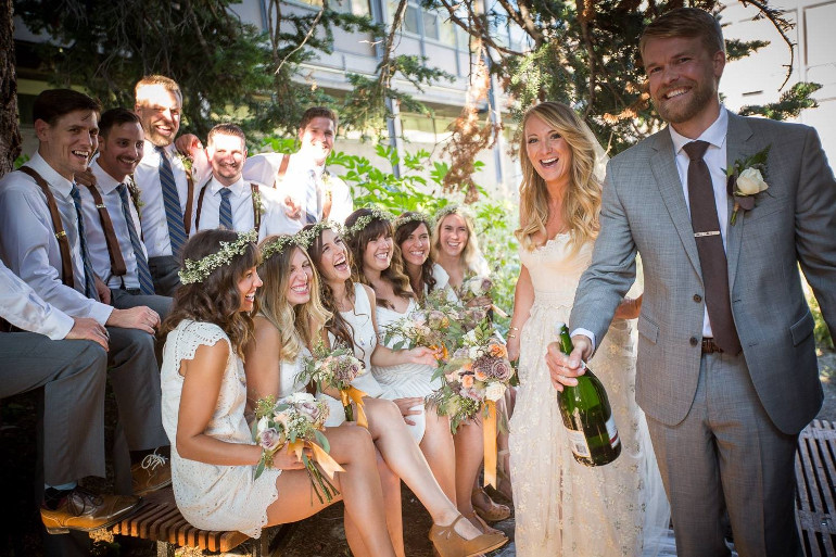 Bride and groom laughing with bridal party | mountain wedding