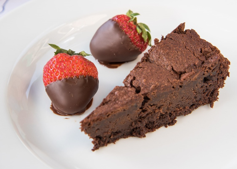 Chocolate cake with chocolate covered strawberries in fine dining restaurant