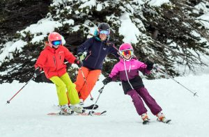 Two kids and their mom having fun skiing the beginner slopes at Alta.