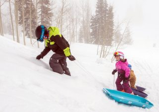 Two kids in ski gear pulling sleds up the hill during outdoor playtime with Kids' Club