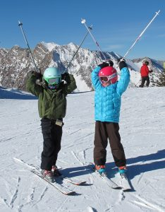 Children having fun skiing on a sunny day during a family ski trip at Alta.