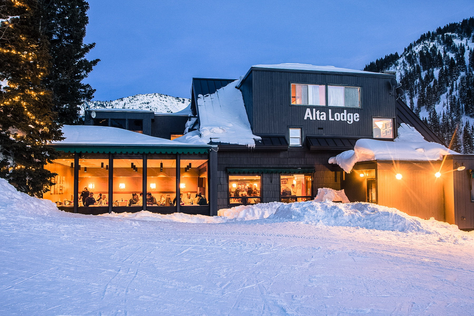 Looking into the bright lights of the Alta Lodge dining room in the evening, from the rope tow hill.